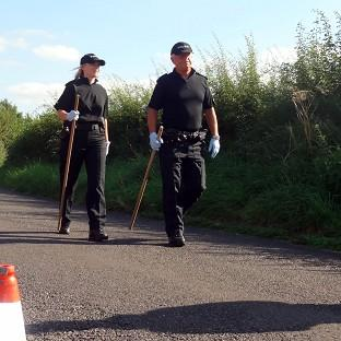 Police close to the scene in a lane in Ashill off the A358 near Ilminster, Somerset, after a young woman was discovered dead in a burning car