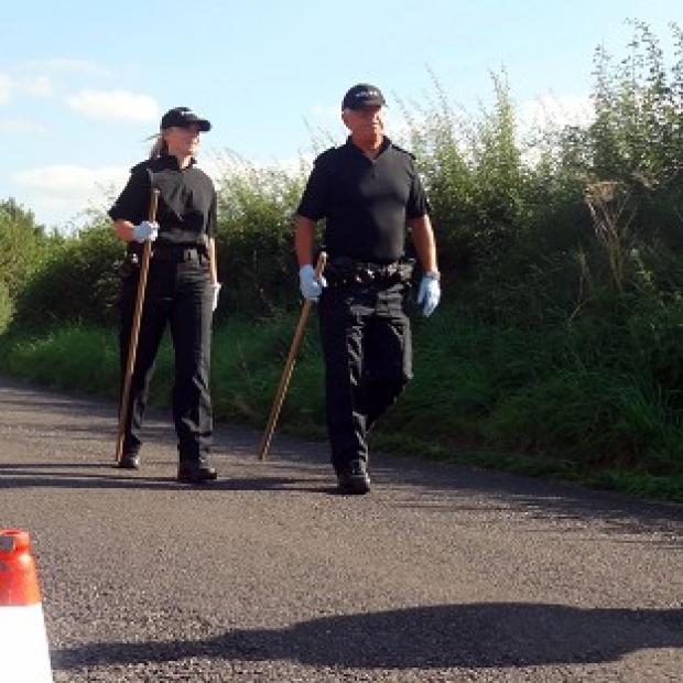 Blackpool Citizen: Police close to the scene in a lane in Ashill off the A358 near Ilminster, Somerset, after a young woman was discovered dead in a burning car
