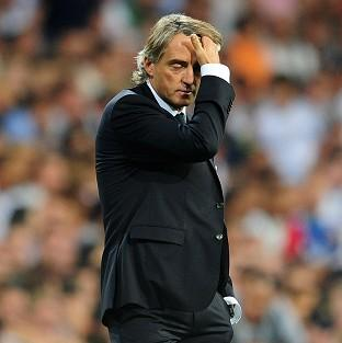 Manchester City's Manager Roberto Mancini stands dejected towards the end of the game against Real Madrid