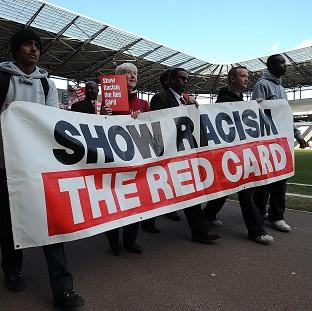 Fans parade a banner saying 'show racism the red card' before a game kicks off