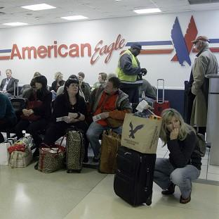 Passengers wait at at LaGuardia airport in New York (AP)