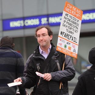 A rail campaigner demonstrates outside King's Cross station in London on the day fares go up