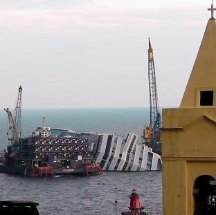 The cruise ship Costa Concordia, leaning on its side, is framed by a church bell tower (AP)