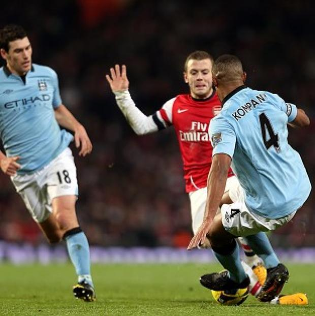 Vincent Kompany, right, challenges Jack Wilshire