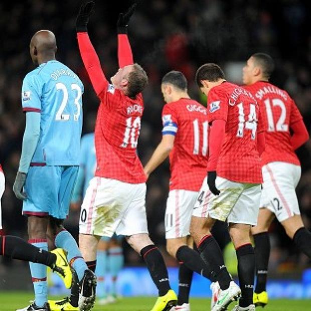 Wayne Rooney, centre, lifts his arms to the sky after scoring in the first half