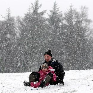 Davie Booth and three year-old daughter Freya sledging in Doune, central Scotland, as snow falls.