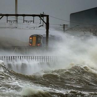 Blackpool Citizen: A train is lashed by waves along the coast at Saltcoats as Scotland has been warned to expect a storm surge.