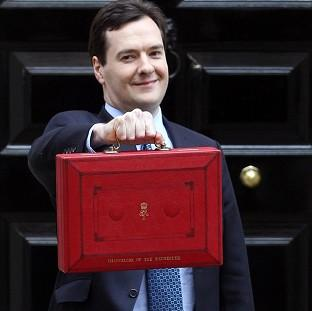 Blackpool Citizen: Chancellor George Osborne holds up his red Ministerial Box outside 11 Downing Street before heading to the Commons to deliver his annual Budget statement