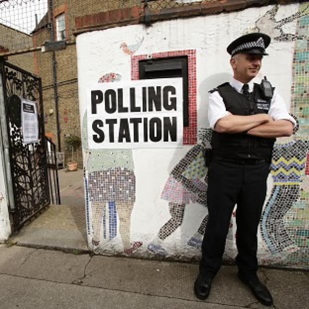 Blackpool Citizen: A police officer outside a polling station in Tower Hamlets