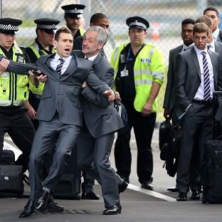 Blackpool Citizen: Comedian Simon Brodkin is taken away from the England team by security at Luton Airport