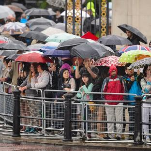 Spectators sheltering from heavy rain as they watched the final rehearsal of Trooping the Colou